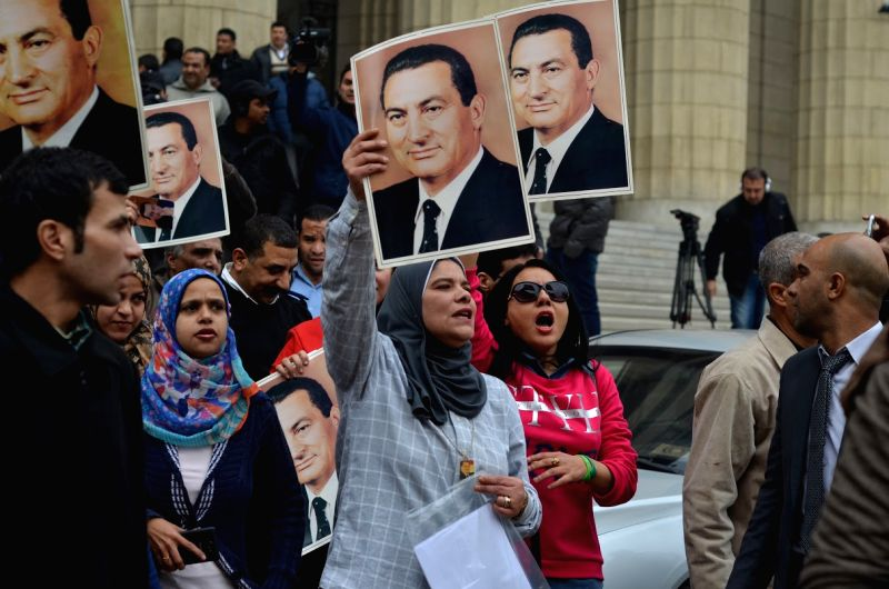 Supporters of ousted Egyptian President Hosni Mubarak hold his portraits and shout slogans outside the court in Cairo, Egypt, on Jan. 13, 2014. Ousted ...