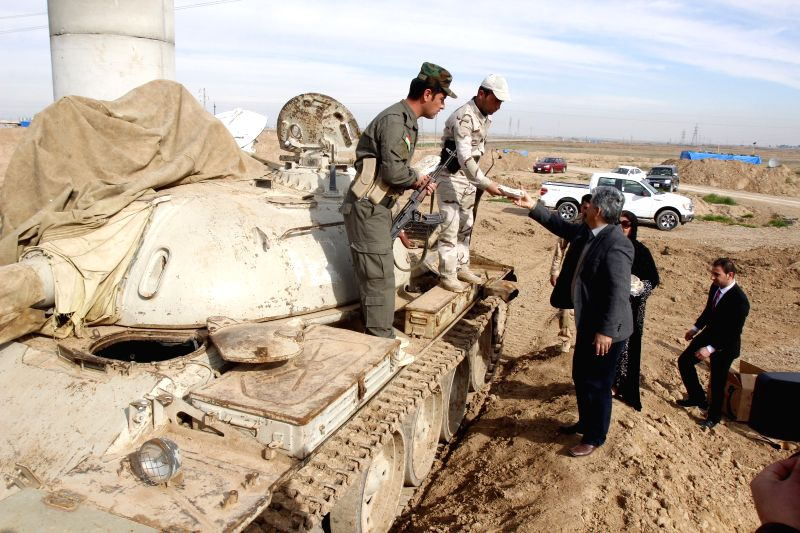 Kurdish civilians hand foods to soldiers of the Kurdish Peshmerga forces stationed at the frontline against Islamic State militants in the Khalid's ...