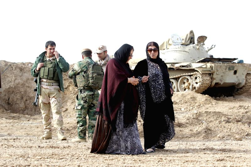 Two women pass by soldiers of the Kurdish Peshmerga forces stationed at the frontline against Islamic State militants in the Khalid's Office, an area 25 .