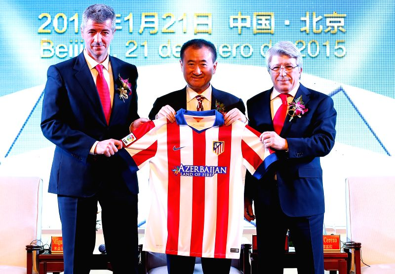 Chairman of Wanda Group Wang Jianlin (C) holds the jersey presented by chairman of Atletico de Madrid Enrique Cerezo (R) and CEO of Atletico de Madrid ..