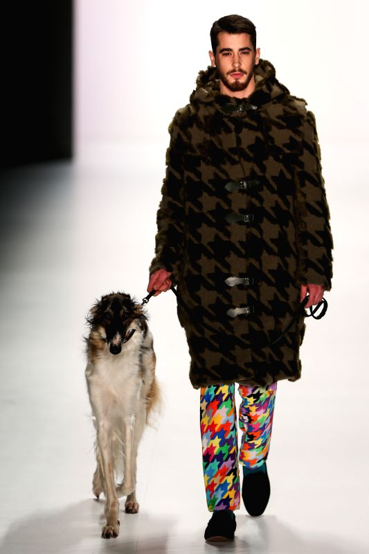 A dog walks along with a model as they display a creation of German designer Rike Feurstein during the Mercedes-Benz Fashion Week Berlin Autumn/Winter ...
