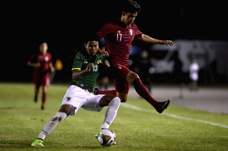 Jeferson Virreira (L) of Bolivia vies with Luiz Da Silva (R) of Peru during a match at the South American U-20 tournament in Colonia, Uruguay, on Jan. ..