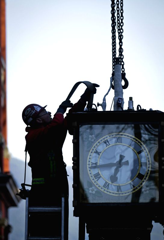 VANCOUVER (CANADA), Jan. 21, 2015 A worker re-installs the steam clock to its original position at Gastown in Vancouver, Canada, Jan. 20, 2015. After a three-month absence ...
