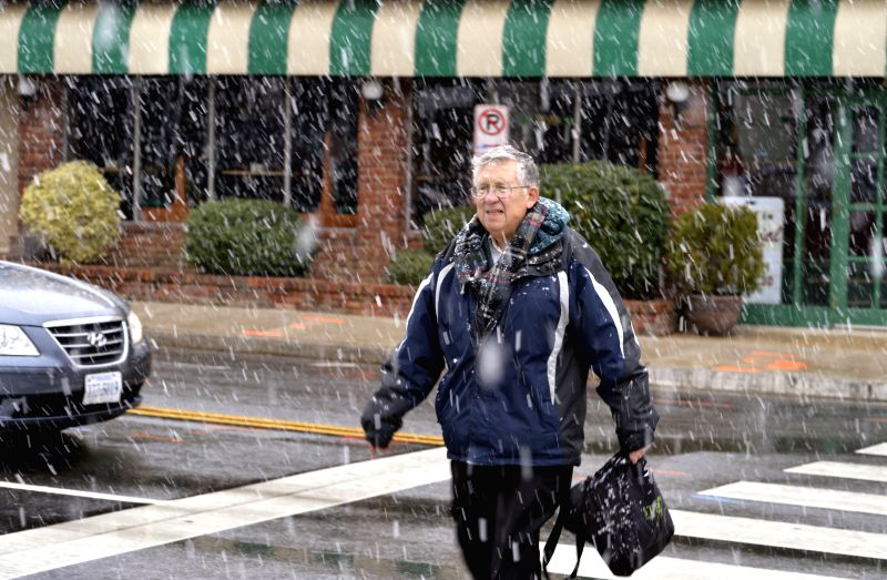 A man walks through snow in Arlington, Virginia, about three kilometers from Washington D.C., the United States, Jan. 21, 2015. (Xinhua/Yin ...