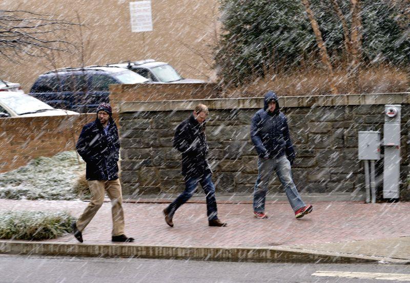 People walk through snow in Arlington, Virginia, about three kilometers from Washington D.C., the United States, Jan. 21, 2015. (Xinhua/Yin ...