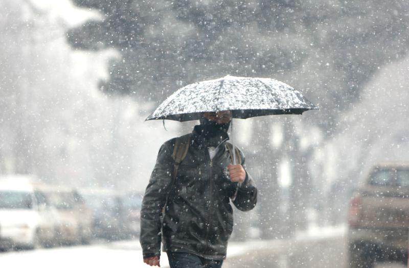 An Afghan man walks in heavy snow in Kabul, Afghanistan, Jan. 25, 2015.
