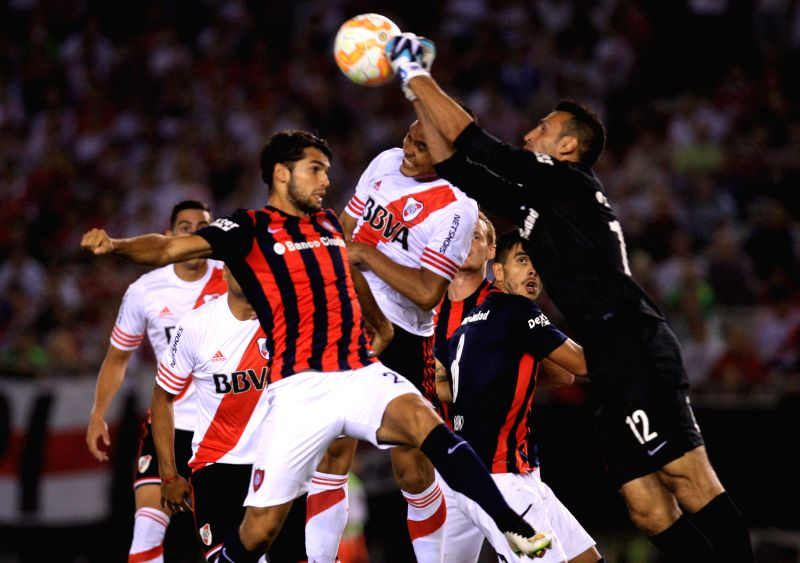 River Plate's Teofilo Gutierrez (C) vies with San Lorenzo's Emanuel Mas (L) and goalkeeper Sebastian Torrico during the match of the South American