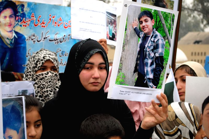A relative holds a photograph of a student who was killed in an attack by Taliban gunmen on Army Public School (APS) during a protest in northwest ...