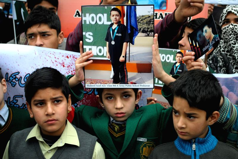 A student holds photographs of a fellow student who was killed in an attack by Taliban gunmen on Army Public School (APS) during a protest in northwest .