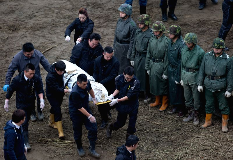 Rescuers transfer the body of a plane crash victim on the bank of Keelung River in Taipei, southeast China's Taiwan, Feb. 7, 2015. Rescuers on Saturday ...