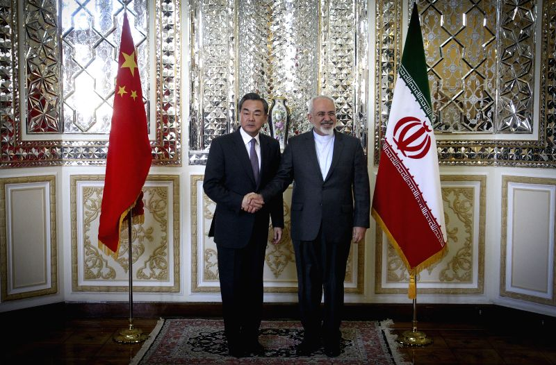 Chinese Foreign Minister Wang Yi (L) shakes hands with his Iranian counterpart Mohammad-javad Zarif during their meeting in Tehran, Iran, on Feb. 15, ... - Wang Y