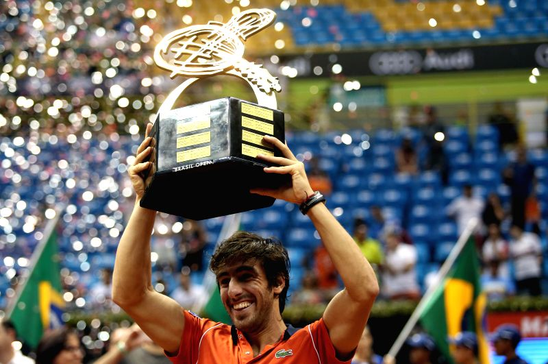 Uruguay's Pablo Cuevas holds a trophy after the final match of the Brazil Open of ATP, against Luca Vanni, of Italy, in Sao Paulo, Brazil, on Feb. 15,