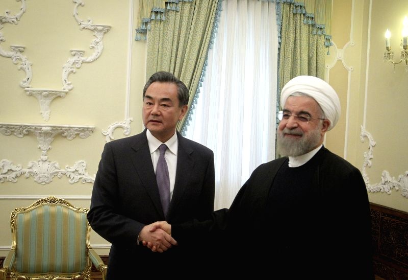 Chinese Foreign Minister Wang Yi (L) shakes hands with Iranian President Hassan Rouhani at the presidential palace in Tehran, Iran, on Feb. 15, 2015. ... - Hassan Rouhani