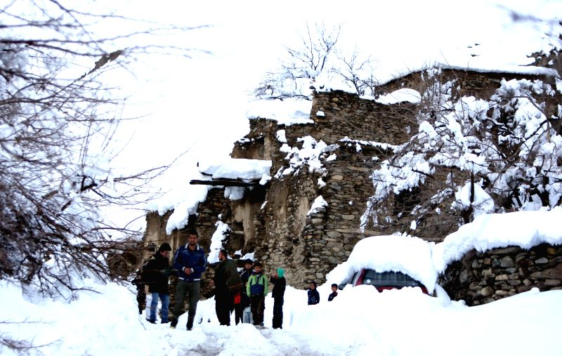 People stand in the snow in Panjshir province, east Afghanistan, on Feb. 25, 2015. The death toll has risen to more than 120 while several of others ...