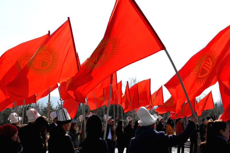 "Kyrgyz people hold national flags during a rally marking the ""National Flag Day"" in Victory Square of Kyrgyzstan's capital Bishkek on March 3, ..."