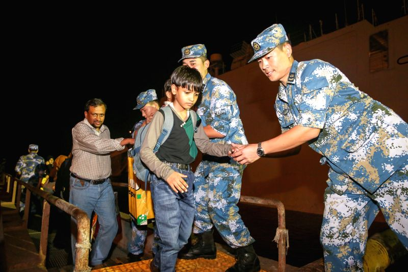 Crew members help people stepping down the Chinese Linyi missile frigate when they arrive in Djibouti, April 2, 2015. A total of 225 nationals from 10 ...