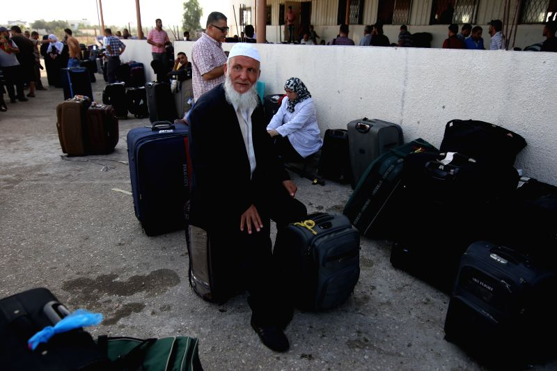 A Palestinian man sits over his luggage as he waits for a travel permit to cross into Egypt at the Rafah border crossing between Egypt and the southern ...