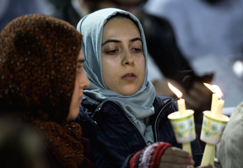 Two Muslim women hold candles as they attend a vigil to pray for the victims of a mass shooting at the San Manuel Stadium in San Bernardino, the ...