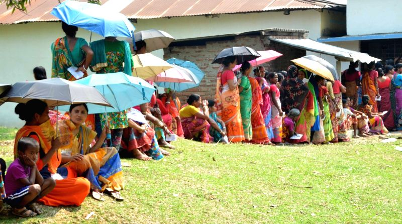 2019 South Dinajpur: Voters use umbrellas to shield themselves from the scorching sun as they wait in a queue to cast their votes for the third phase of 2019 Lok Sabha elections, at a polling station in West Bengal's South Dinajpur, on April 23, 2019