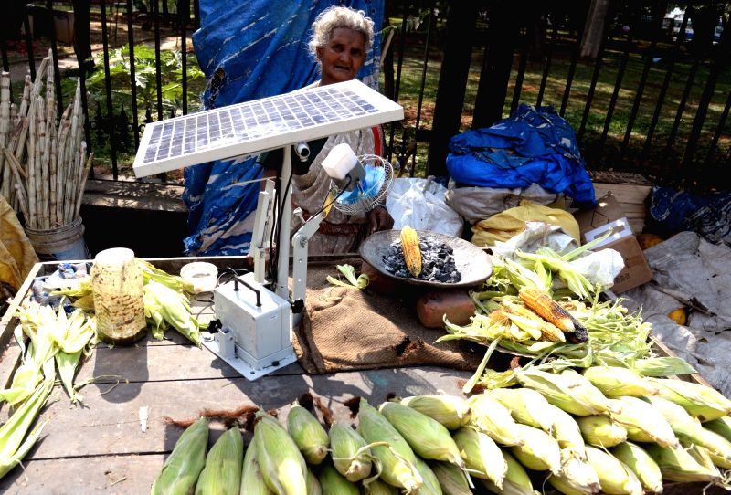 75-year-old Selvamma who has been selling corn outside Vidhana Soudha building for over 20 years and used to constantly fan the coal to roast corn, now using a solar powered fan to grill ...