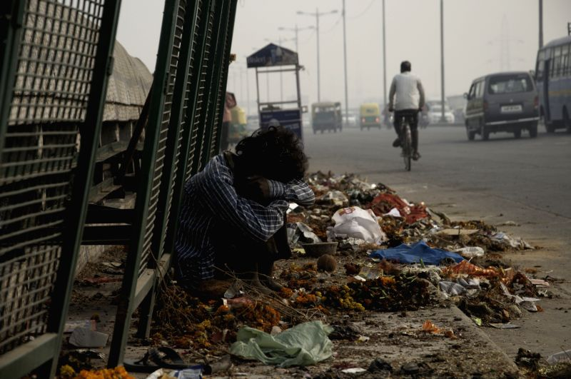 A beggar sits beside a pile of garbage in New Delhi on Oct.31, 2015.