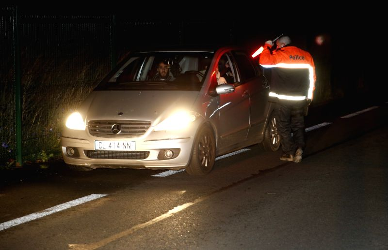 A Belgian policeman checks a car entering France at Belgian border city Bettignies, Nov. 14, 2015. Over 100 people have been reportedly killed and many more ...