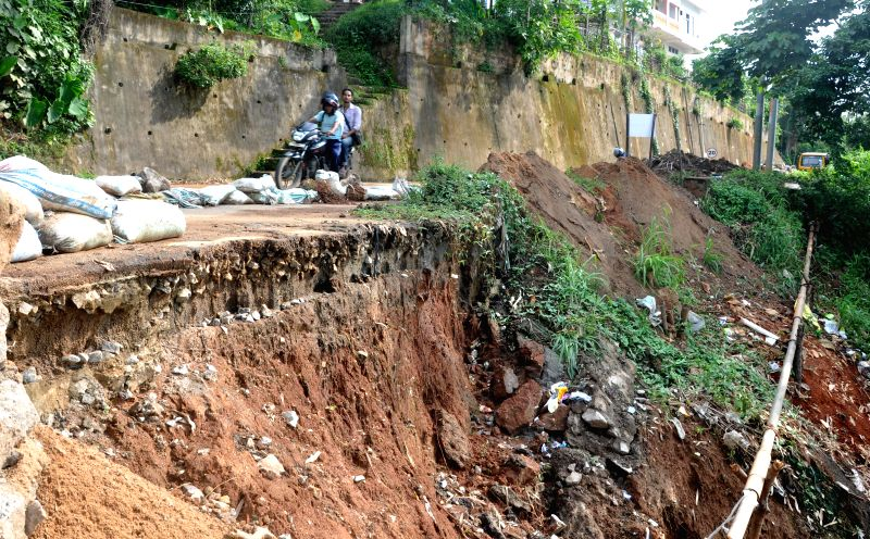 A biker moves cautiously as he travels on a road a portion of which got destroyed in a landslide in Guwahati on July 8, 2014.
