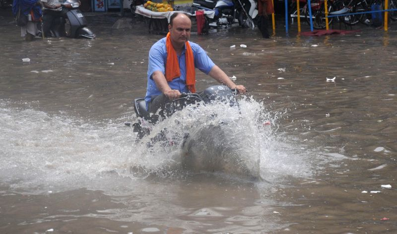 A biker rides on a flooded road of Amritsar after heavy rains on August 1, 2014.