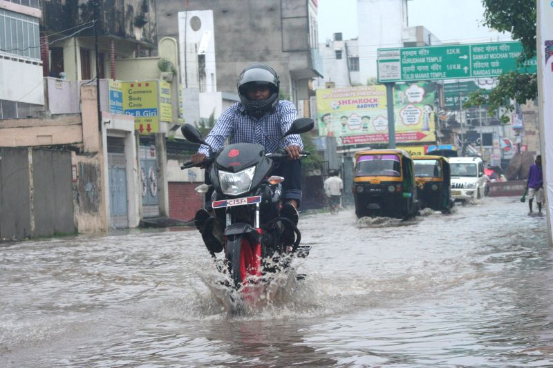 A biker struggles through waterlogged streets of Varanasi after heavy showers on Aug 12, 2014.