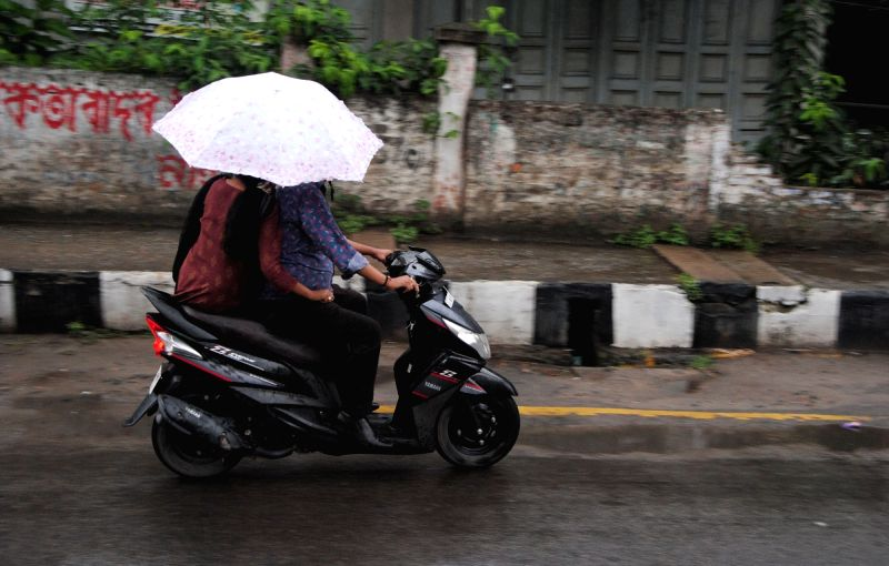 A biker use umbrella to shield from rains in Guwahati on May 14, 2016.
