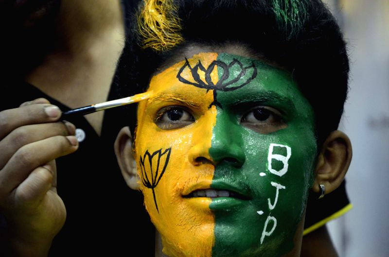 A BJP supporter gets his face coloured in party's colours in Mumbai on May 15, 2014.