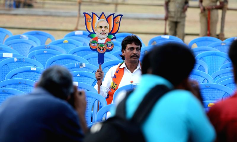 A BJP supporter sits holding the symbol of the party at the venue of BJP Prime Ministerial candidate and Gujarat Chief Minister Narendra Modi's rally in Chennai on April 13, 2014. - Narendra Modi