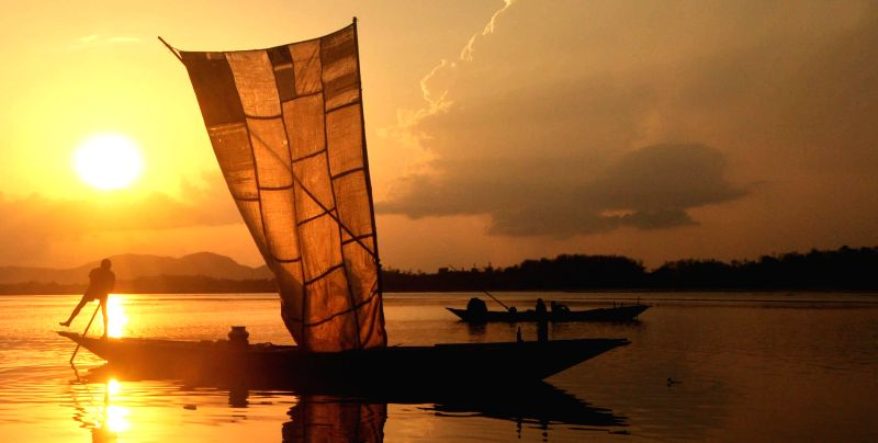 A boatman with his boat on the Brahmaputra river during sunset near Guwahati on May 11, 2014.