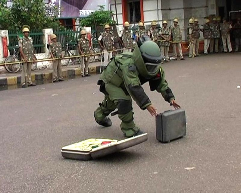 A bomb-squad personnel tries to open an abandoned suitcase found near Varanasi Cantt Railway Station on Aug 12, 2014. However, after opening it no explosives were found.