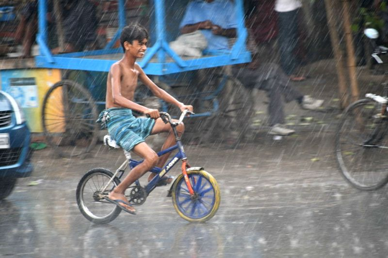 A boy enjoys cycle ride during rains, in Patna on June 12, 2018.