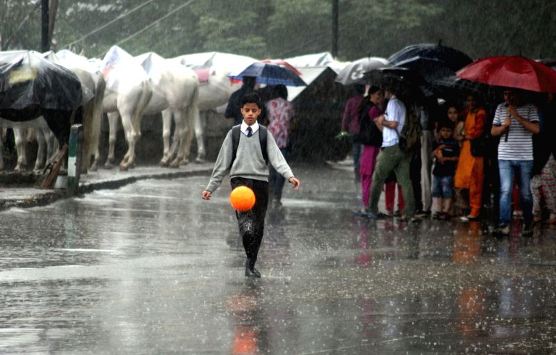 A boy plays with a football during rains, in Shimla on July 18, 2018.
