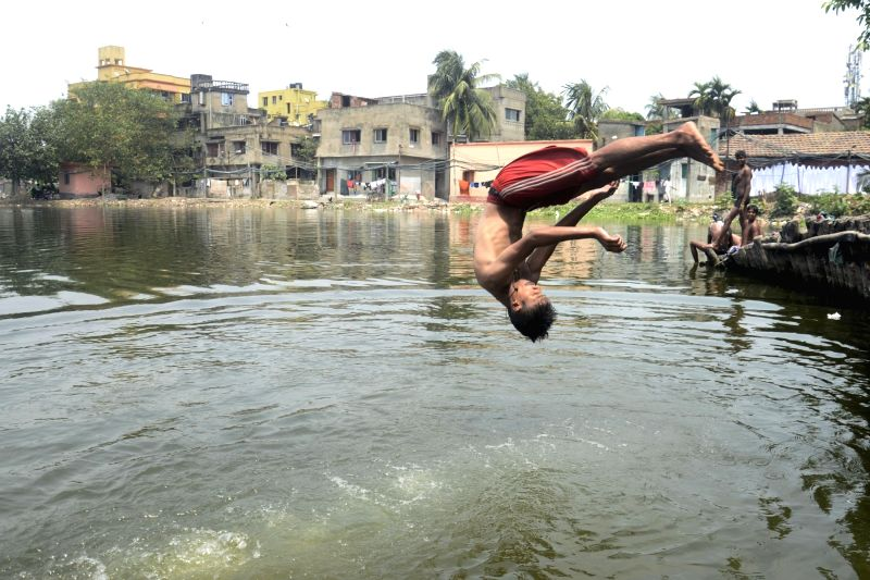 A boy plunges into a pond to beat the heat on a hot day in Kolkata on May 21, 2017.