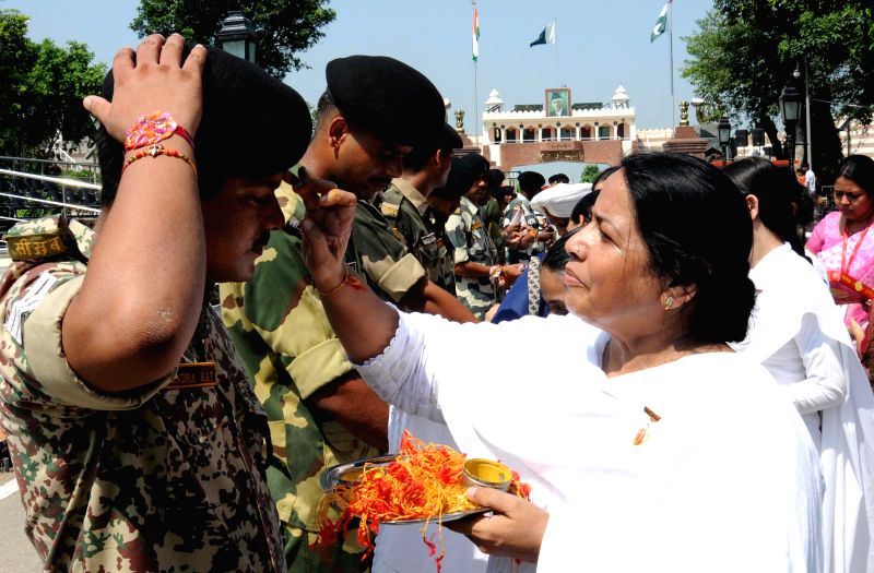 A Bramha Kumari ties Rakhis to the soldiers deployed at Wagha border on Raksha Bandhan on Aug 10, 2014.