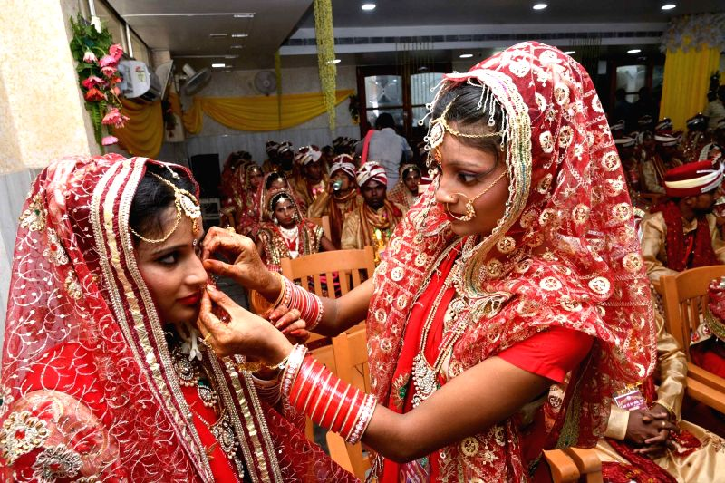 A bride helps a fellow bride in wearing a nose ring during a mass marriage ceremony, in Patna on July 15, 2018.