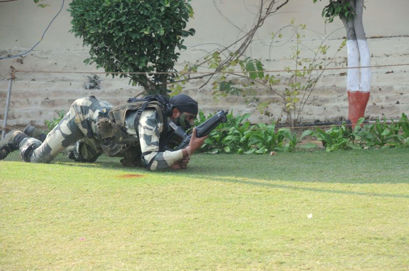 A BSF commandos demonstrates his skills during a mock anti insurgency operation ahead of BSF Raising Day in New Delhi on Nov 26, 2014.