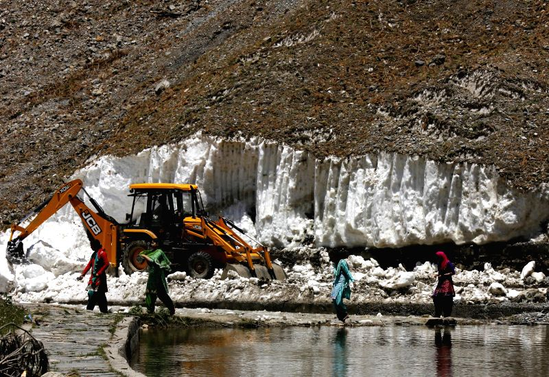 A bulldozer clears snow from the Amarnath Yatra route in Baltal, 15 km away from Sonamarg in Ganderbal district of Jammu and Kashmir on June 29, 2014.