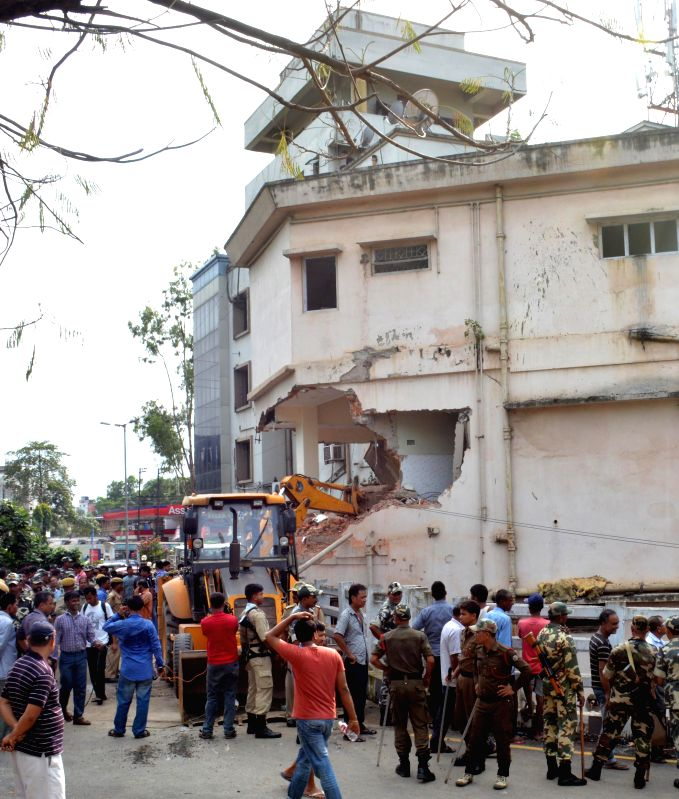 A bulldozer demolishes a portion of a building during Kamrup Metropolitan district administration's demolition drive against illegal structures in Guwahati on July 8, 2014.