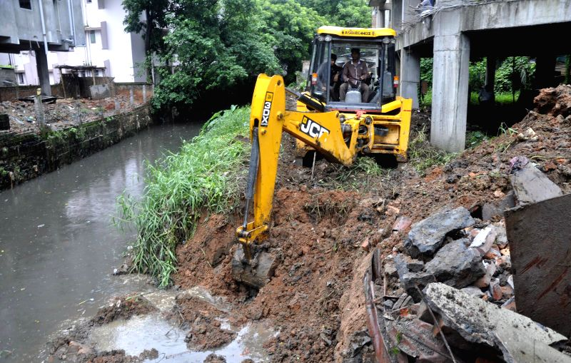 A bulldozer demolishes a portion of an illegal structure during Kamrup Metropolitan district administration's demolition drive against illegal structures in Guwahati on July 8, 2014.