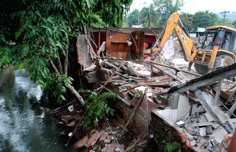 A bulldozer demolishes a portion of an illegal structure during Kamrup Metropolitan district administration's demolition drive against illegal structures in Guwahati on July 9, 2014.