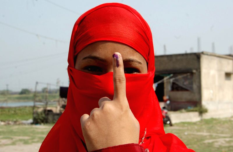 A burqa clad woman shows her fore finger marked with phosphoric ink after casting her vote during the seventh phase of 2014 Lok Sabha Polls in Sreerampur of West Bengal on April 30, 2014.
