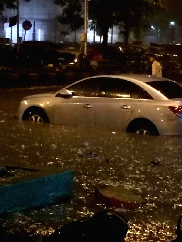 A car gets stuck on a waterlogged road of Mumbai on July 16, 2014.