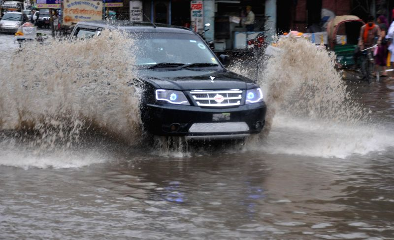 A car plies on waterlogged streets of Amritsar after rains on June 25, 2014.