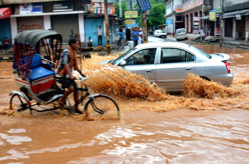 A car struggle through the waterlogged streets of Guwahati after heavy showers on Aug 10, 2014.