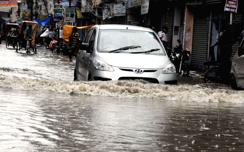 A car struggles through a waterlogged road of Patna on Aug 13, 2014.