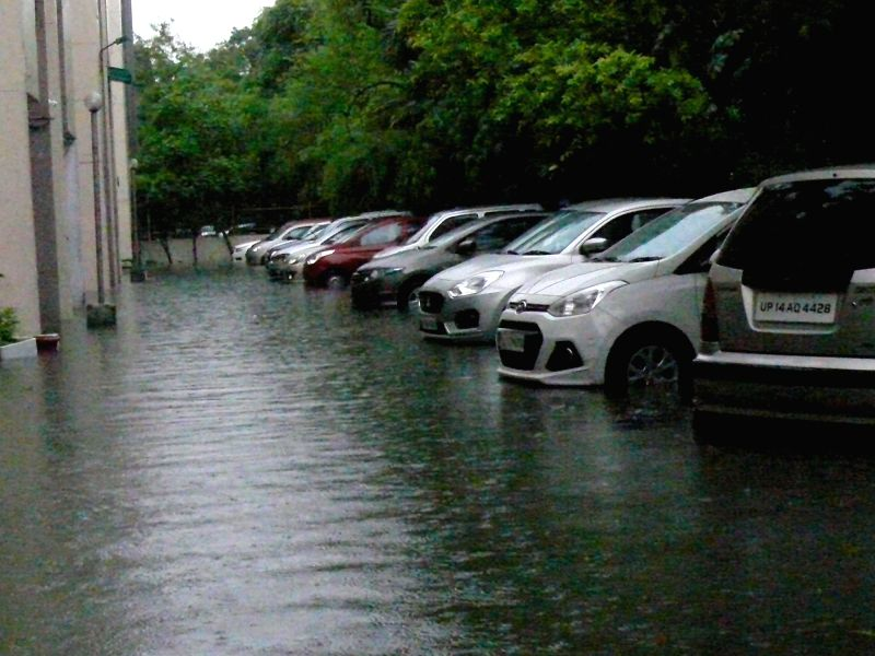 A car wades through water logged street after a heavy downpour in New Delhi on July 26, 2018.